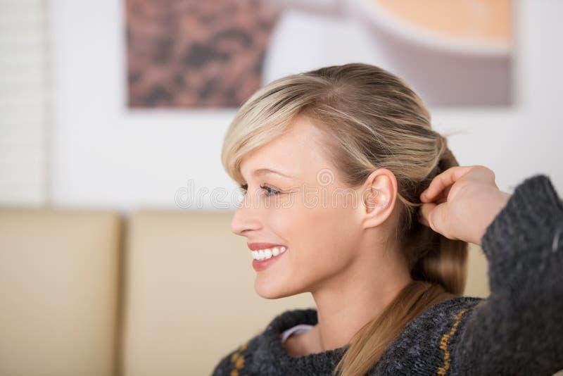 Donna sorridente seducente che gioca con i suoi capelli fotografia stock