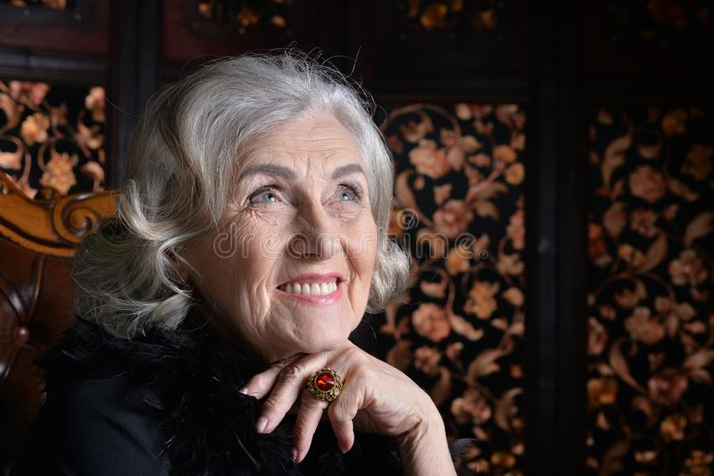 Donna sorridente senior in boa che posa a casa fotografia stock