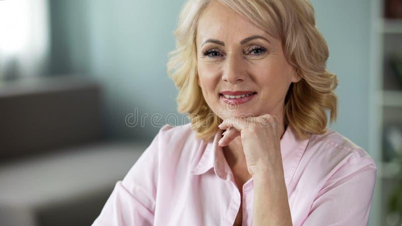 Donna sorridente soddisfatta con il suo fondo pensioni, pensionato felice che esamina macchina fotografica fotografia stock libera da diritti