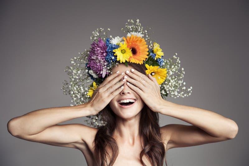 Donna sorridente sorpresa con la corona del fiore sulla sua testa immagine stock