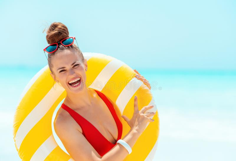 Donna sorridente sul litorale che indossa salvagente gonfiabile giallo fotografia stock libera da diritti