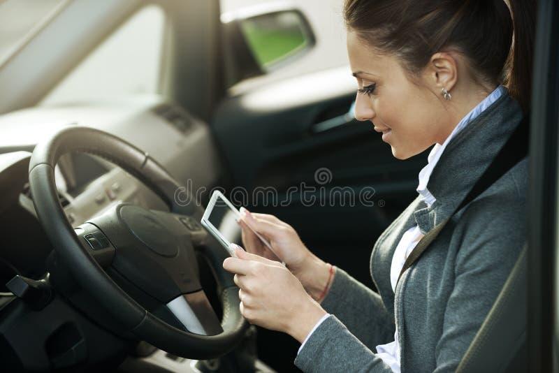 Donna sorridente in un'automobile con la compressa fotografie stock libere da diritti
