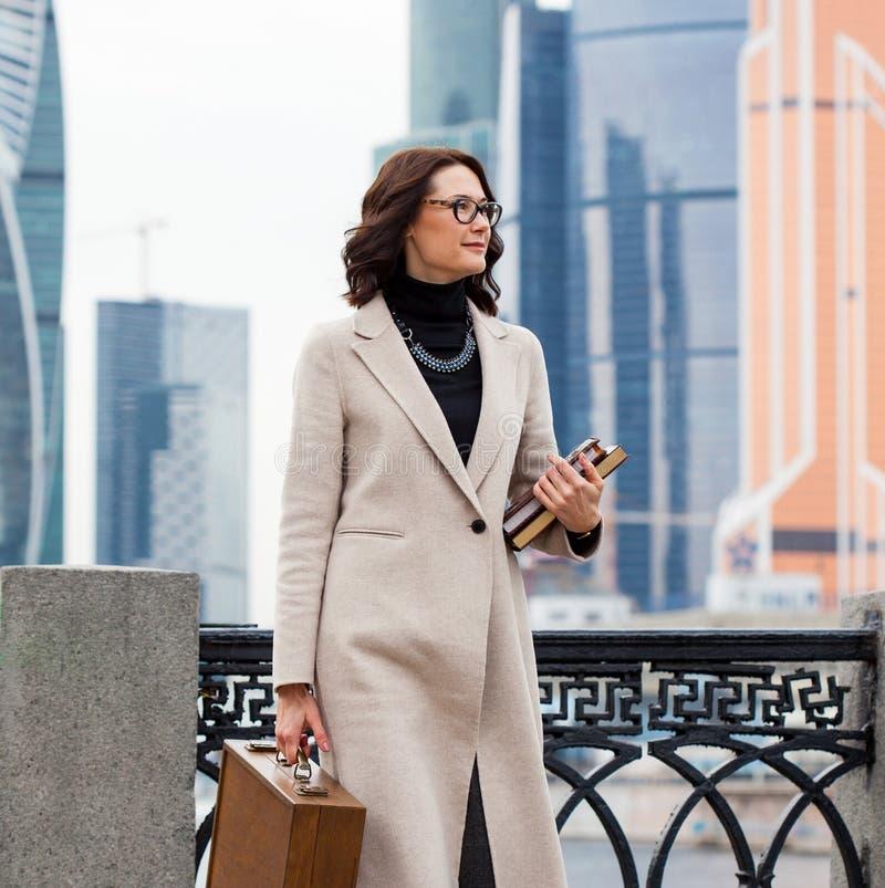 Donna sorridente in un cappotto leggero con una cartella ed i libri fotografia stock