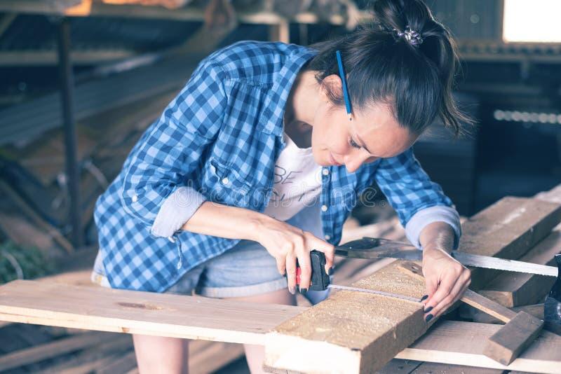 Donna sorridente in una misura di nastro di misurazione dell'officina domestica un bordo di legno prima di segare, carpenteria fotografie stock libere da diritti