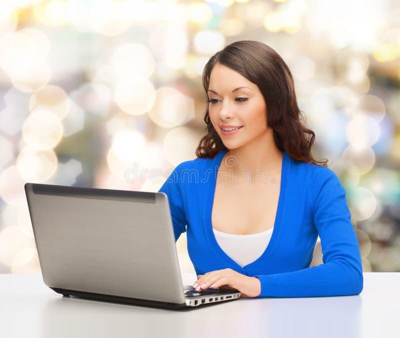 Donna sorridente in vestiti blu con il computer portatile immagini stock