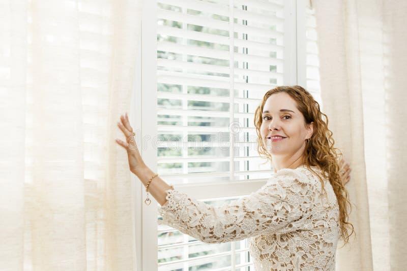 Donna sorridente vicino alla finestra fotografia stock libera da diritti