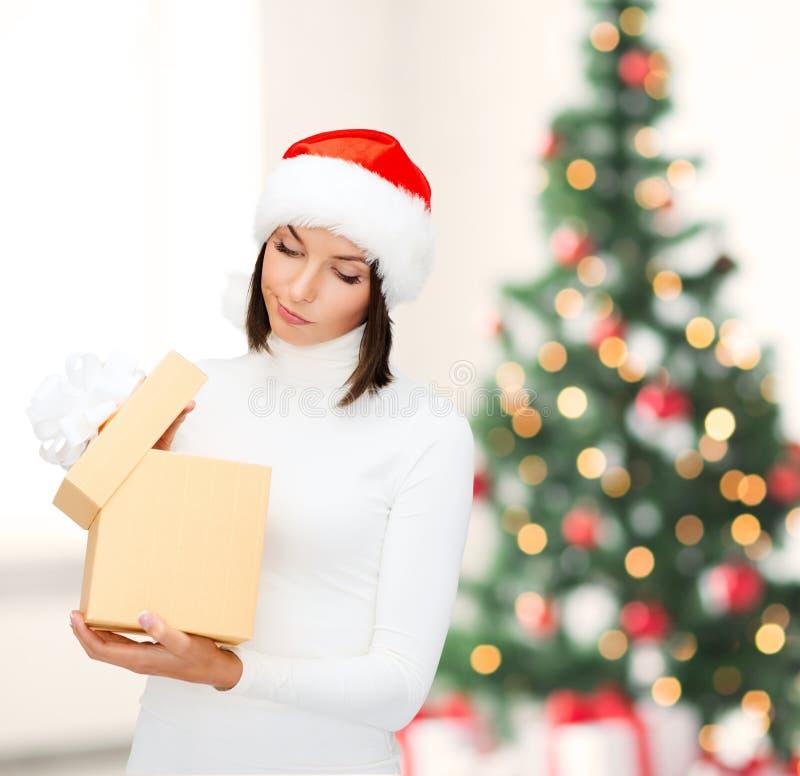 Donna sospettosa in cappello dell'assistente di Santa con il contenitore di regalo immagine stock libera da diritti