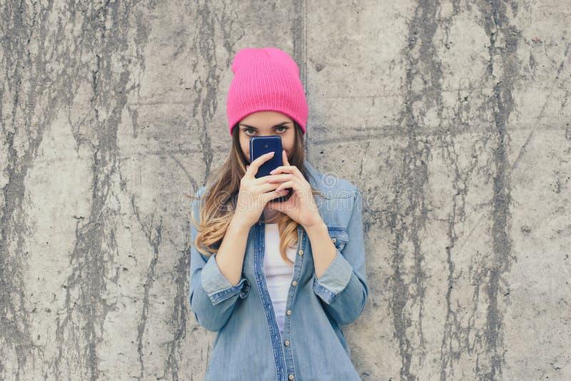 Donna sospettosa o timida in abbigliamento casual e cappello rosa che nascondono il suo fronte dietro lo smartphone, ha letto le  fotografia stock