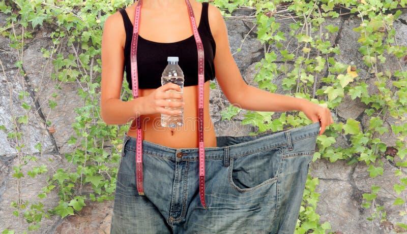 Donna sottile attaccata in pantaloni enormi fotografie stock libere da diritti