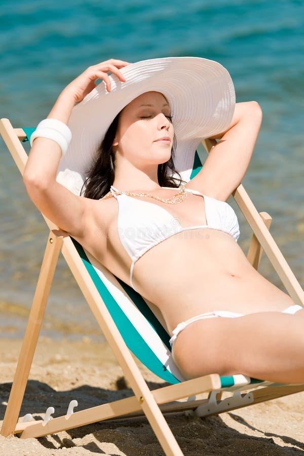 Donna sottile di estate che prende il sole nel deckchair del bikini immagine stock libera da diritti