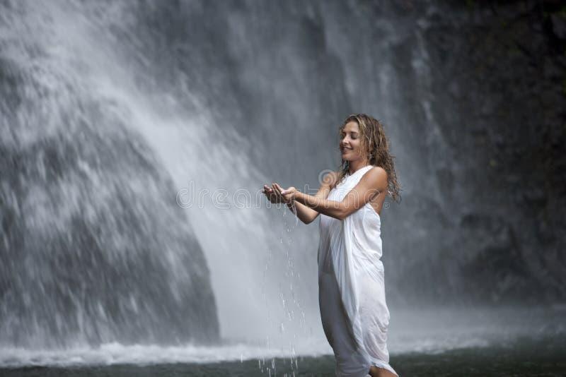 Donna sotto la cascata fotografie stock libere da diritti