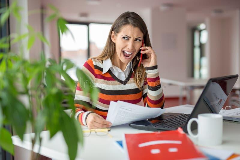 Donna sottolineata di affari che grida sul telefono fotografia stock