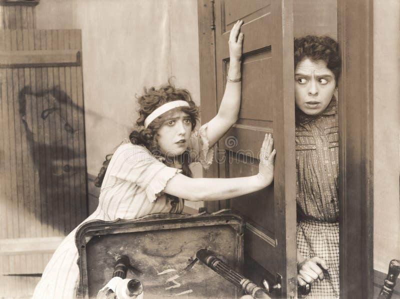 Donna spaventata che prova a tenere l'altra donna da stanza immagine stock