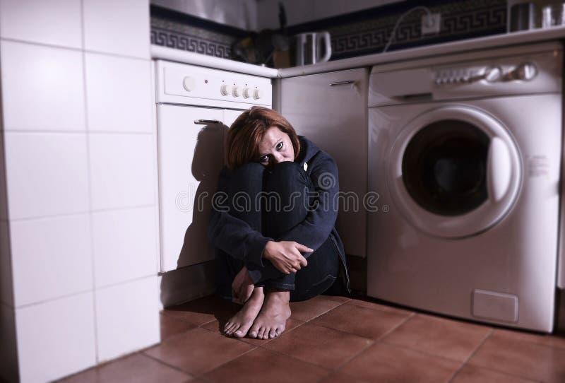 Donna spaventata e malata sola che si siede sul pavimento della cucina nella depressione di sforzo e nella tristezza fotografia stock