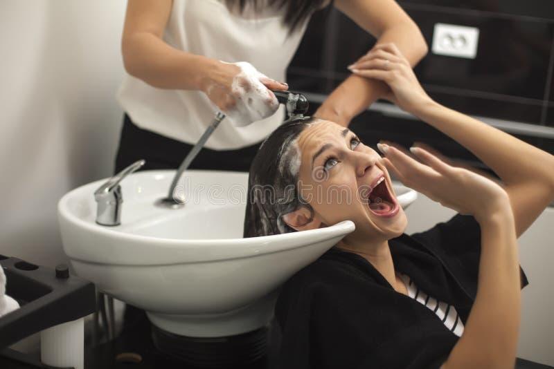 Donna spaventata in un salone di capelli immagine stock