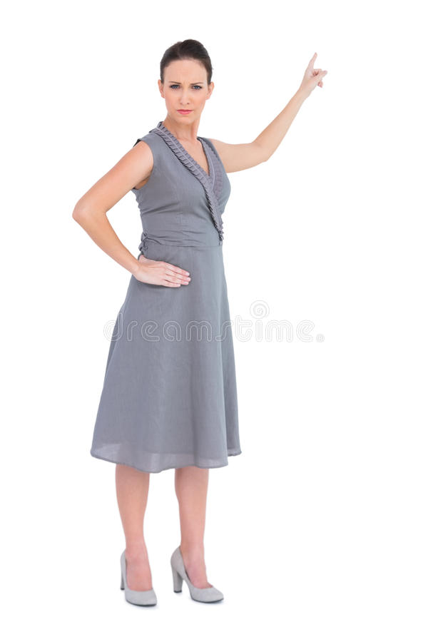 Donna splendida aggrottante le sopracciglia in vestito di classe che indica direzione immagine stock libera da diritti