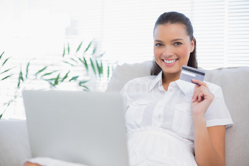 Donna splendida allegra che compra online facendo uso del computer portatile fotografia stock