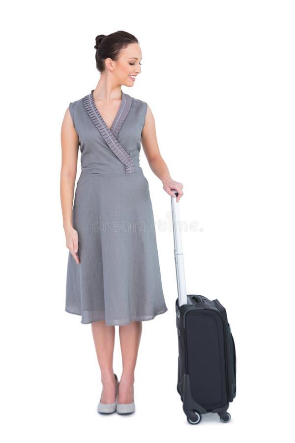 Donna splendida allegra che posa con la sua valigia fotografia stock