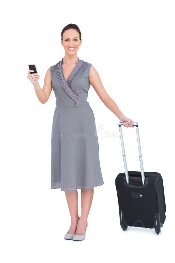 Donna splendida allegra con suo mandare un sms della valigia fotografia stock libera da diritti