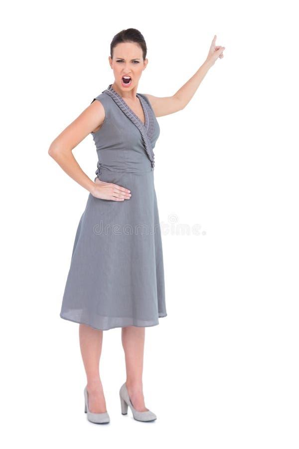 Donna splendida arrabbiata in vestito di classe che indica dito su fotografia stock