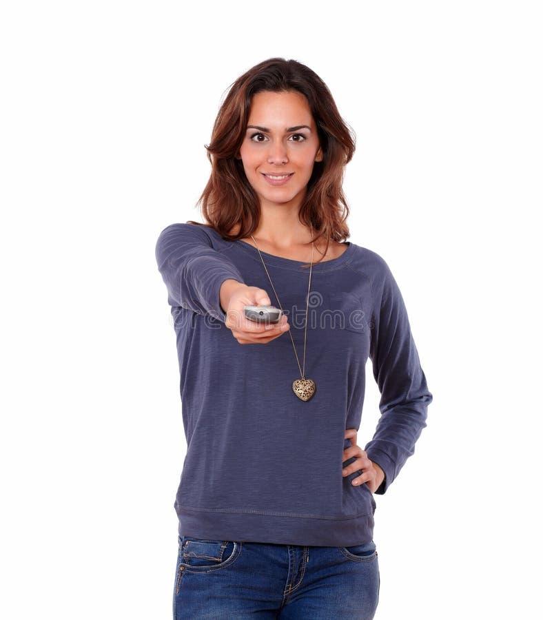 Donna splendida che indica il telecomando fotografia stock libera da diritti
