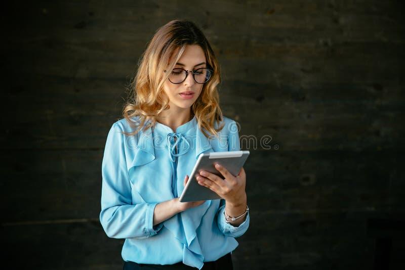 Donna splendida di affari in occhiali facendo uso di una compressa fotografie stock libere da diritti