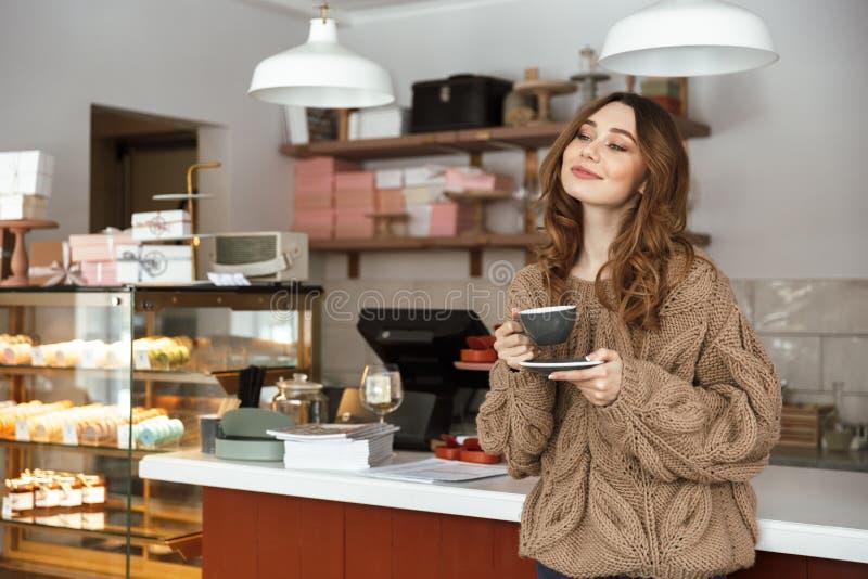 Donna splendida in maglione che guarda da parte e che sorride, mentre holdi fotografia stock