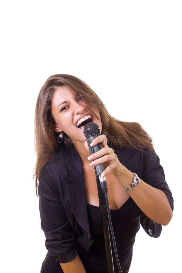 Donna splendida nel microfono ed in canto neri della tenuta del vestito immagine stock