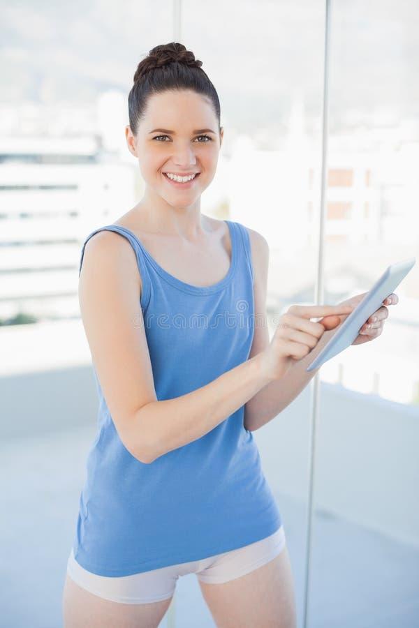 Donna splendida sorridente in abiti sportivi facendo uso del pc della compressa immagine stock