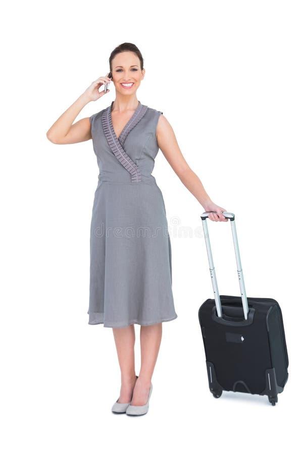 Donna splendida sorridente che porta la sua valigia che ha telefonata fotografie stock