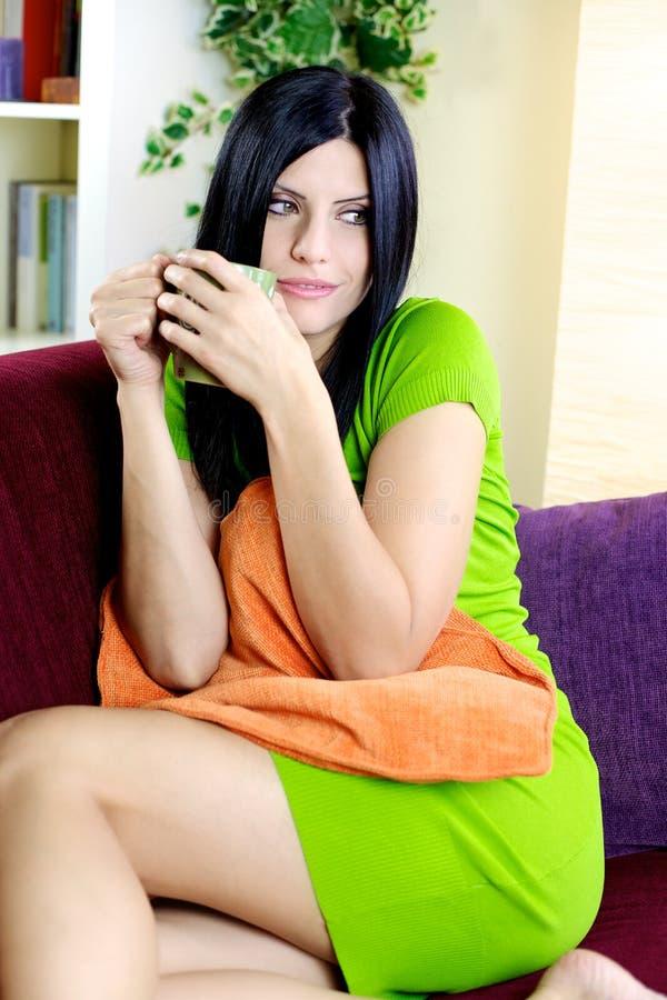 Donna splendida sorridente con il caffè bevente del vestito verde a casa fotografia stock