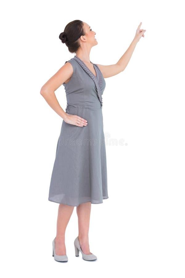 Donna splendida sorridente in vestito di classe che precisa direzione fotografia stock libera da diritti