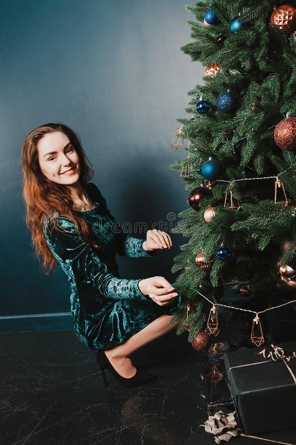 Donna splendida in un bello vestito accanto all'albero di Natale con i contenitori di regalo, sorridenti Concetto della decorazio fotografia stock libera da diritti
