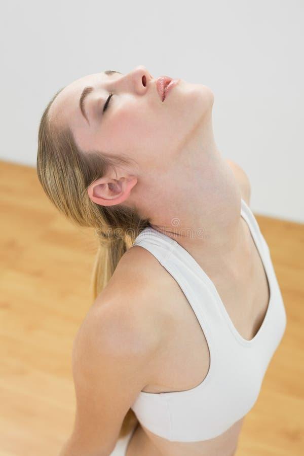 Donna sportiva adorabile che allunga inginocchiamento sul pavimento nella palestra immagini stock libere da diritti