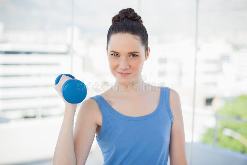 Donna sportiva allegra che si esercita con la testa di legno immagine stock