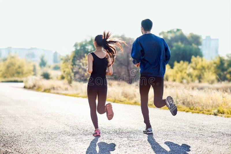 Donna sportiva attiva ed uomo che pareggiano il giorno soleggiato immagine stock
