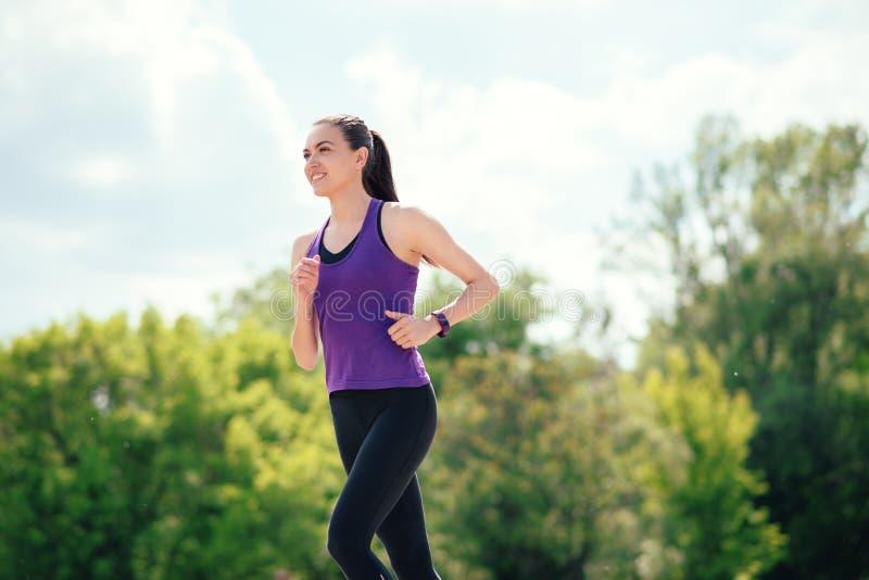 Donna sportiva attraente che corre nel parco Giorno soleggiato per lo sport fotografia stock