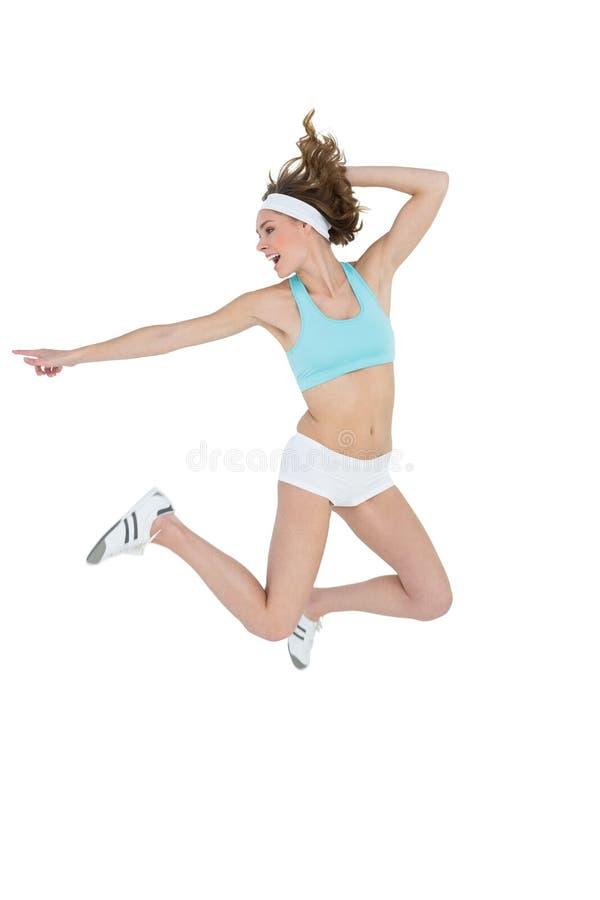 Donna sportiva attraente che salta mentre indicando immagine stock
