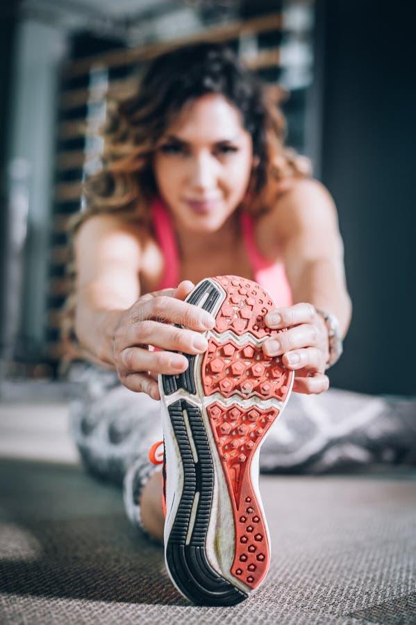 Donna sportiva attraente di forma fisica che allunga nella palestra moderna fotografia stock libera da diritti