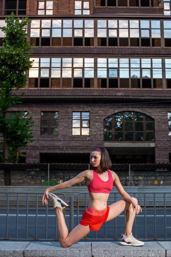 Donna sportiva che allunga e che si scalda le gambe prima dell'eseguire allenamento urbano di forma fisica Sport e concetto sano  immagini stock libere da diritti
