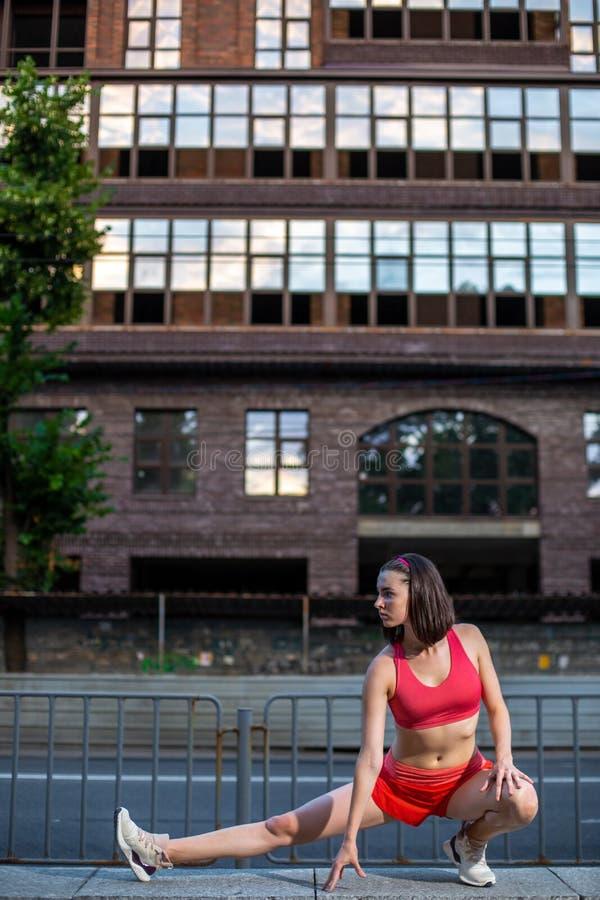 Donna sportiva che allunga e che si scalda le gambe prima dell'eseguire allenamento urbano di forma fisica Sport e concetto sano  immagine stock
