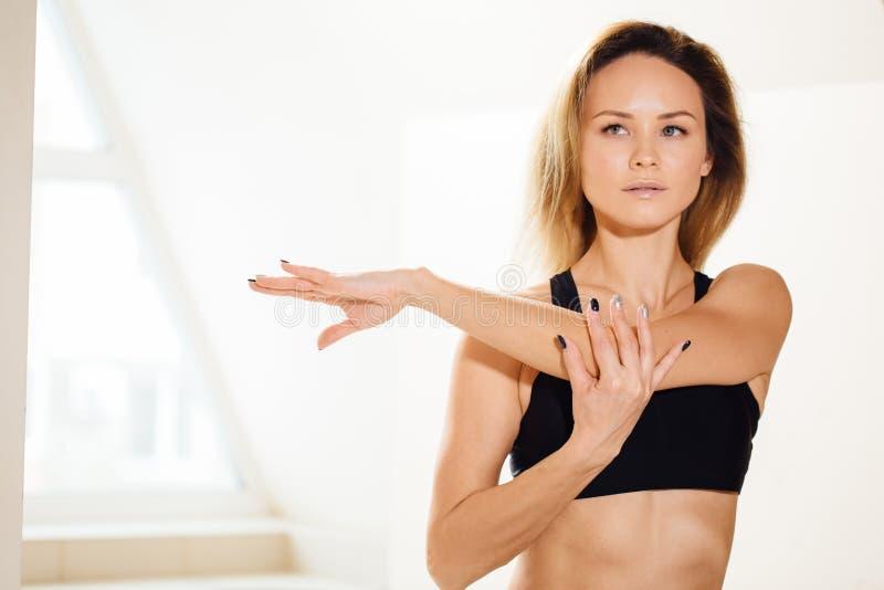 Donna sportiva che allunga le mani alla classe di yoga nello studio di forma fisica immagine stock libera da diritti