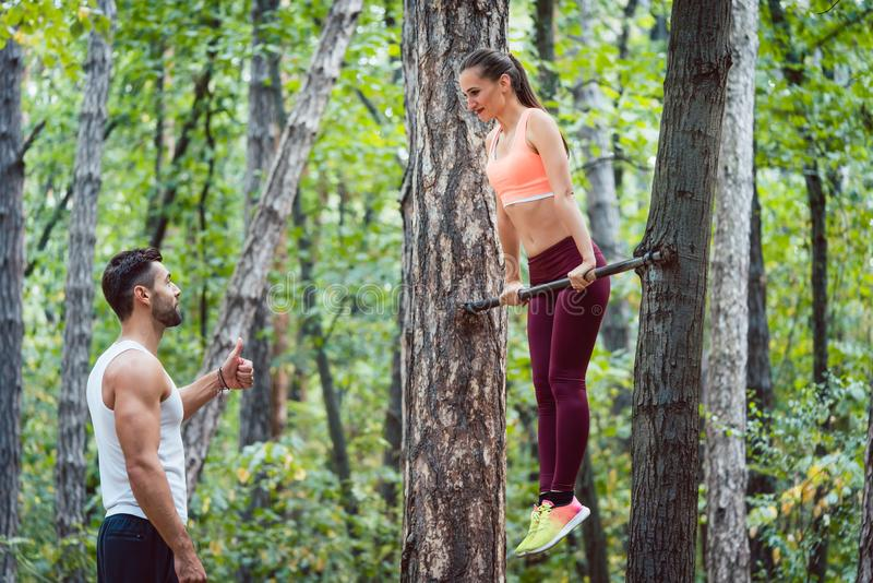 Donna sportiva che fa esercizio di forma fisica sulla sbarra fotografia stock libera da diritti