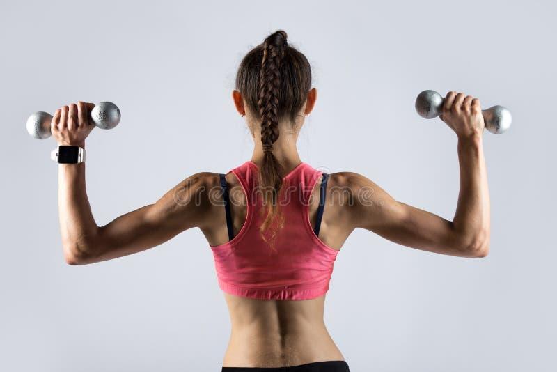 Donna sportiva che risolve con i pesi Vista posteriore fotografie stock libere da diritti