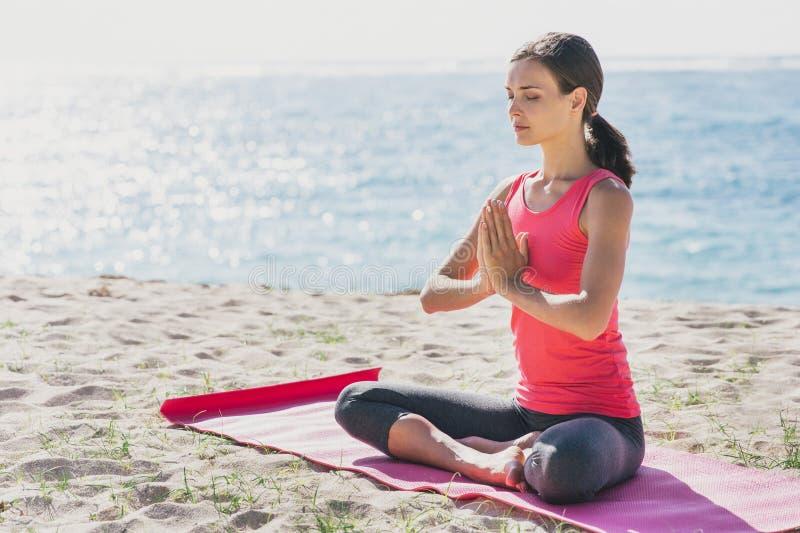 Donna sportiva che ritiene pacifica facendo meditazione immagine stock