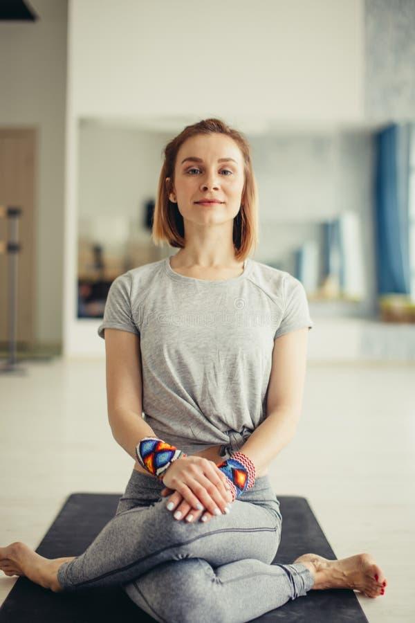 Donna sportiva che si siede a gambe accavallate nella posa del loto nella stanza luminosa fotografia stock libera da diritti
