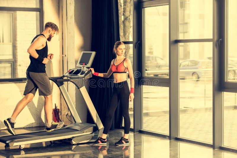 Donna sportiva che sta vicino all'addestramento barbuto dello sportivo sulla pedana mobile fotografia stock