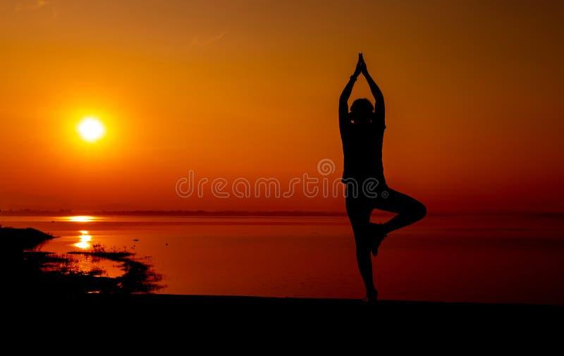 Donna sportiva della siluetta con il tramonto Attività di esercizio e sana fotografia stock