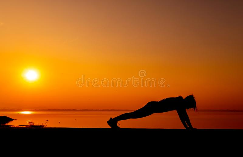 Donna sportiva della siluetta con il tramonto Attività di esercizio e sana immagine stock libera da diritti