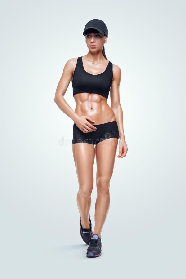 Donna sportiva di forma fisica che cammina sul fondo bianco fotografia stock libera da diritti